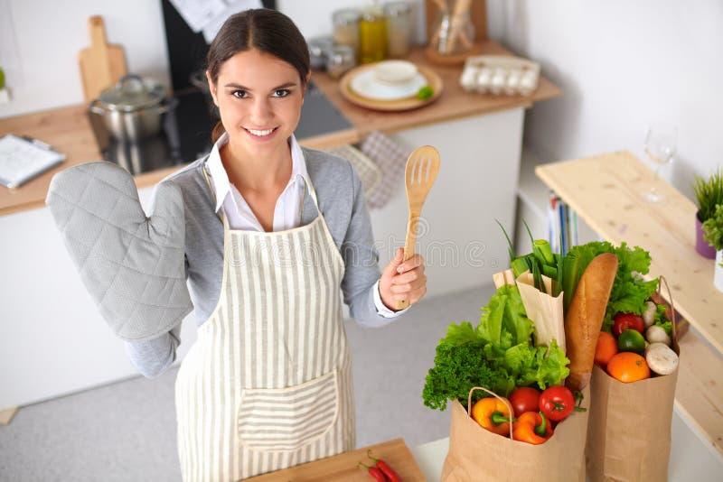 Женщина делая здоровую еду стоя усмехающся внутри стоковая фотография