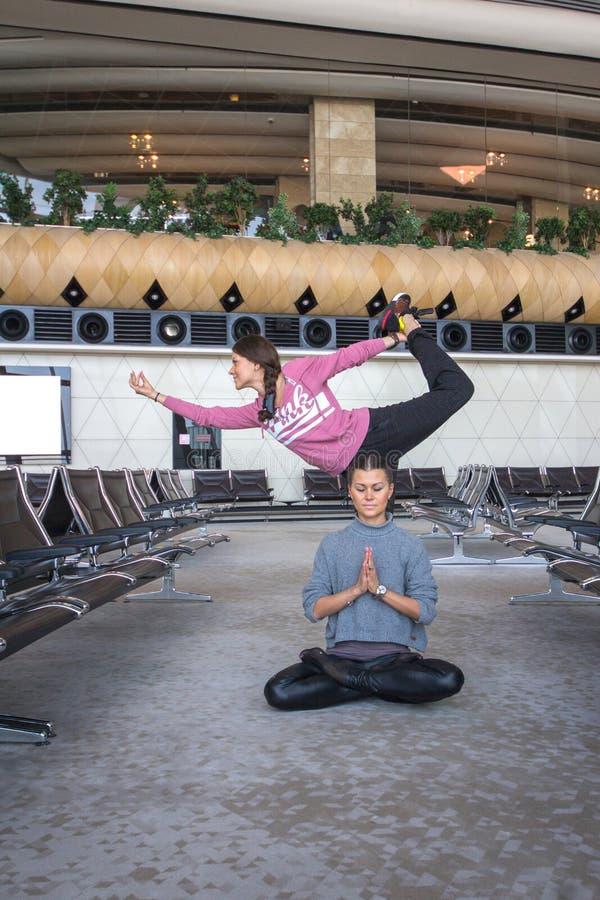 Женщина делая йогу в зале авиапорта стоковая фотография