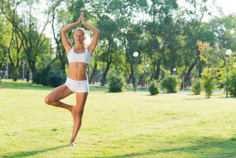Женщина делая йогу в парке стоковые фото