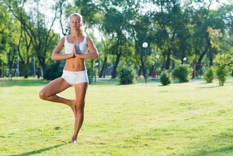Женщина делая йогу в парке стоковые фотографии rf