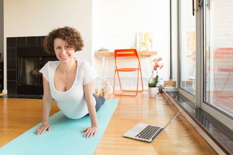 Женщина делая йогу с онлайн app на компьютере в ее живущей комнате стоковые изображения rf