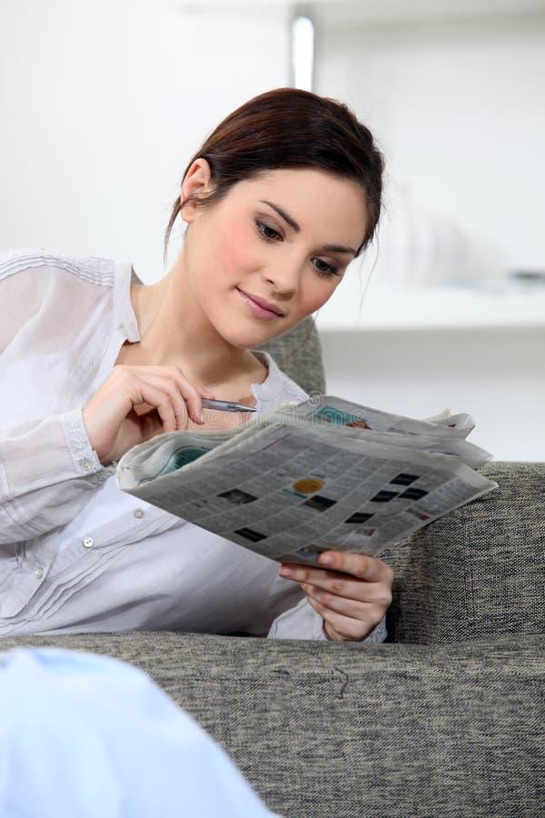 Женщина делая кроссворды стоковое изображение