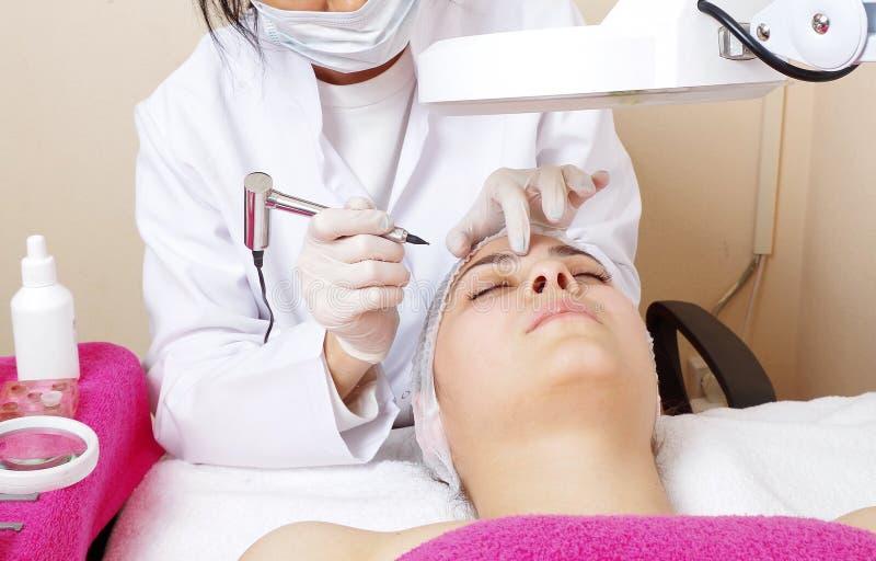 Женщина делая процедуру по чела стоковое изображение