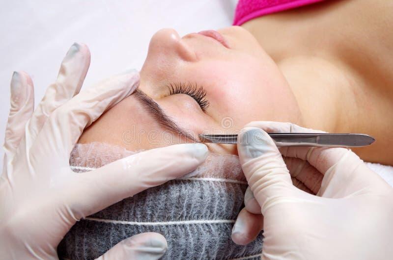 Женщина делая процедуру по чела стоковая фотография rf