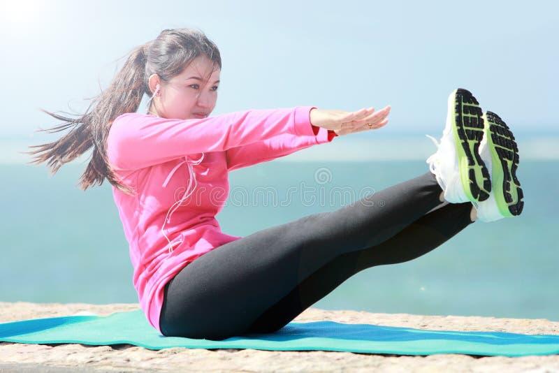 Женщина делая разминку в пляже стоковое изображение
