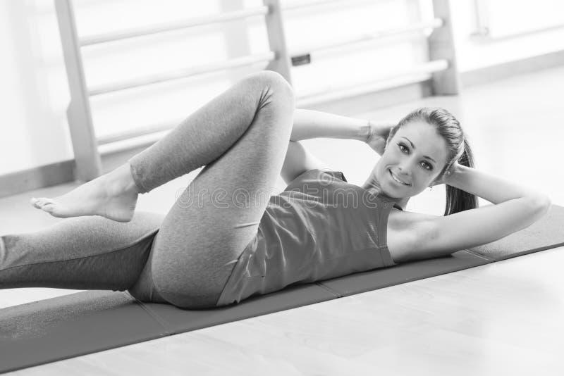 Женщина делая разминку abs на спортзале стоковые изображения