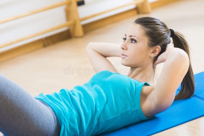 Женщина делая разминку abs на спортзале стоковые фотографии rf