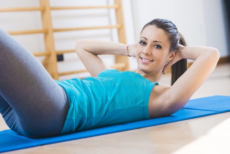 Женщина делая разминку abs на спортзале стоковое изображение rf