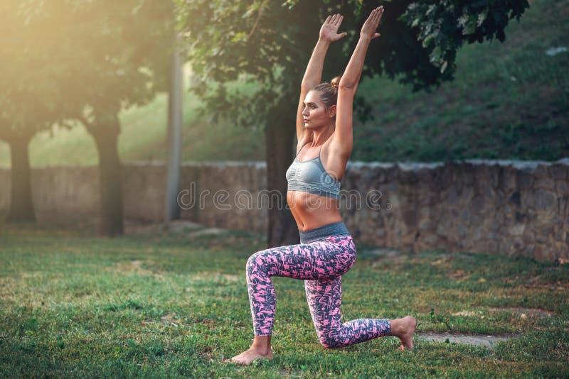 Женщина делая тренировку йоги в парке лета стоковое фото rf