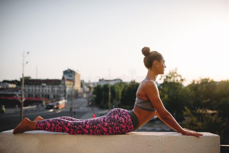 Женщина делая тренировку йоги, город на предпосылке стоковые фотографии rf