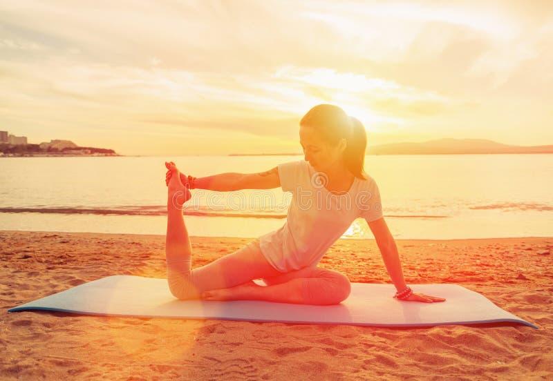 Женщина делая тренировку йоги на заходе солнца стоковое фото