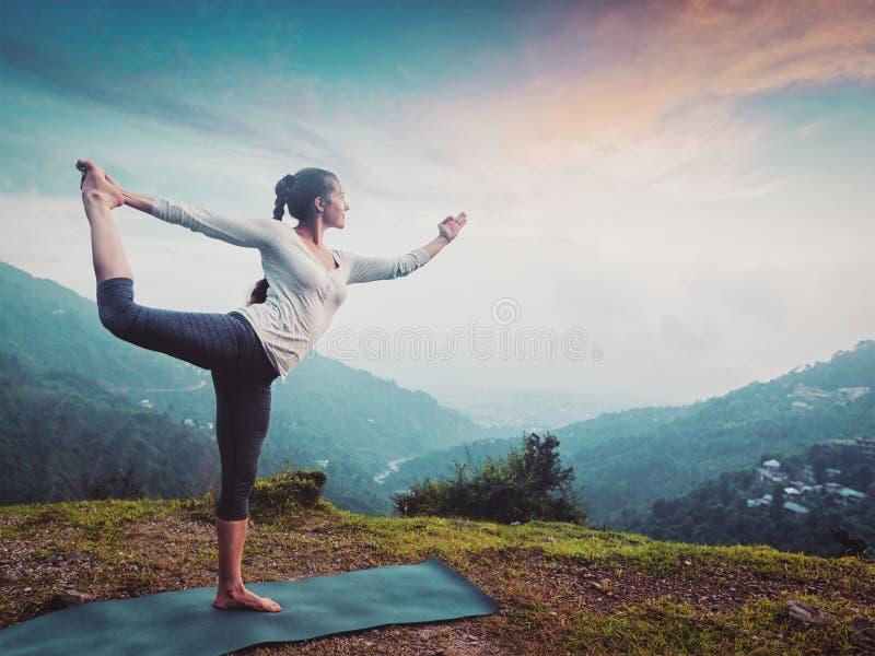 Женщина делая asana Natarajasana йоги outdoors на водопаде стоковые фото