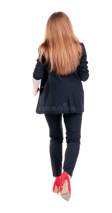 женщина дела идущая задний взгляд идя маленькая девочка в костюме Re стоковая фотография