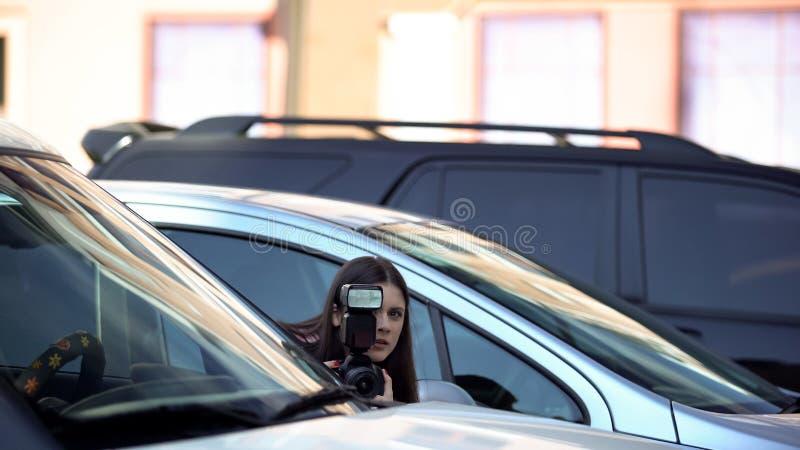 Женщина-журналист с камерой, прячущаяся на стоянке, ищет сенсацию стоковое фото
