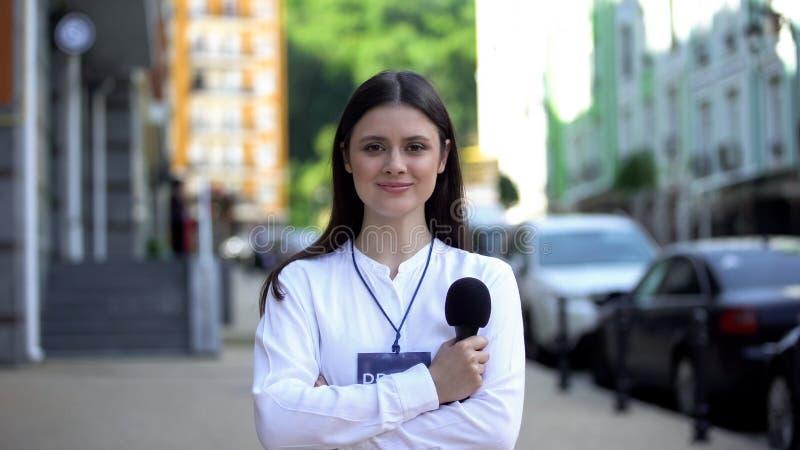 Женщина-журналист с микрофоном и пропуском для прессы, смотрящая на камеру на улице стоковые изображения rf