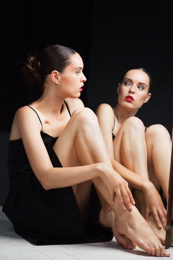 Женщина заботит ее ноги около зеркала над чернотой стоковое фото