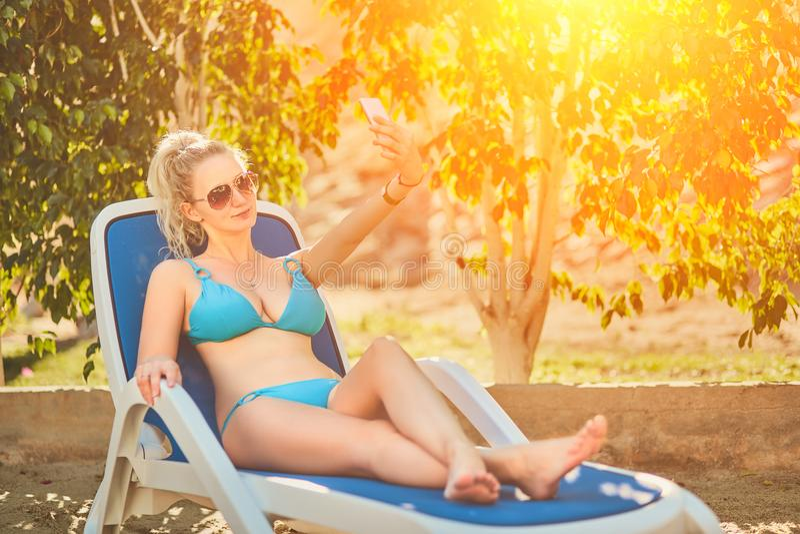 Женщина загорая в бикини на тропическом курорте Красивая женщина лежа на lounger солнца Пирофакел Солнця стоковое фото rf
