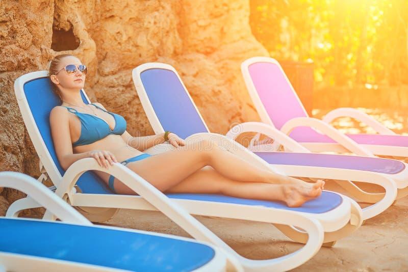 Женщина загорая в бикини на тропическом курорте Красивая женщина лежа на lounger солнца Пирофакел Солнця стоковое изображение rf