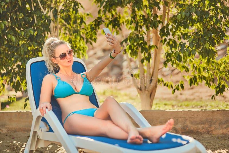 Женщина загорая в бикини на тропическом курорте Красивая женщина лежа на lounger солнца стоковое фото rf