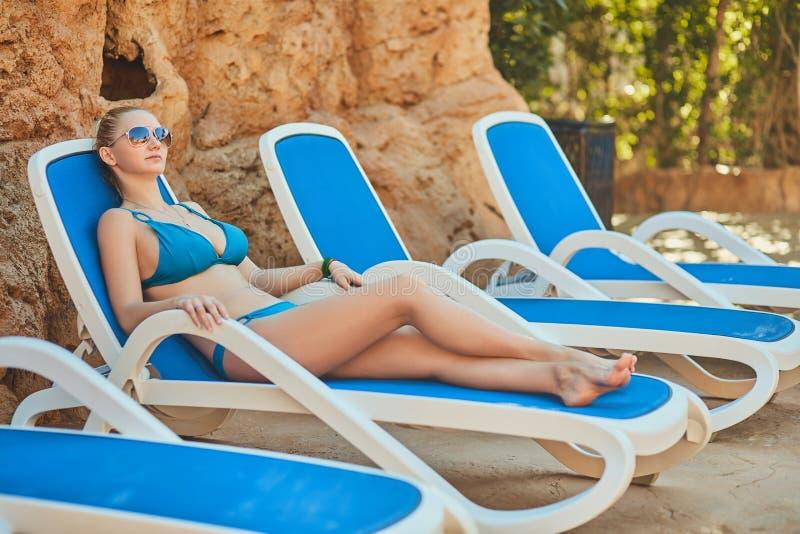 Женщина загорая в бикини на тропическом курорте Красивая женщина лежа на lounger солнца стоковое изображение rf