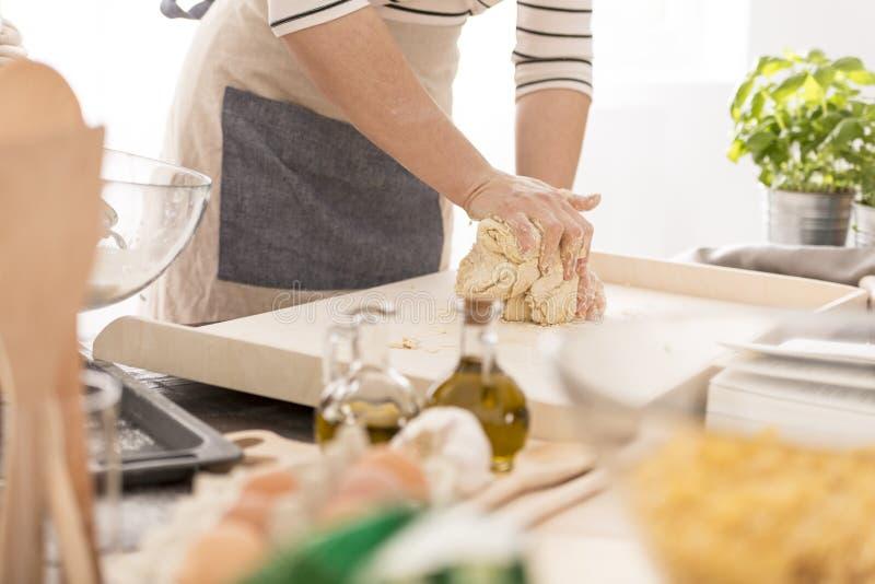 Женщина замешивая тесто стоковое фото rf
