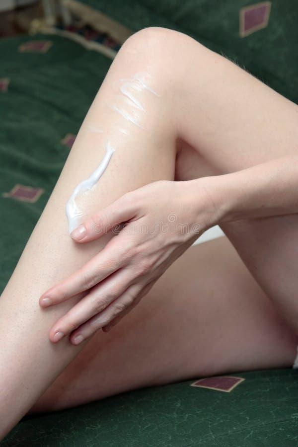 женщина затирания s лосьона ноги руки стоковое изображение rf