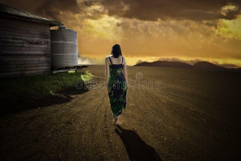 женщина захода солнца гуляя стоковое изображение rf