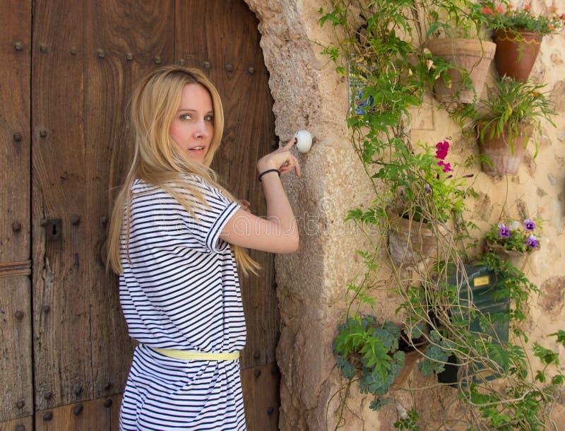 Женщина звеня на дверном звонке стоковое изображение rf
