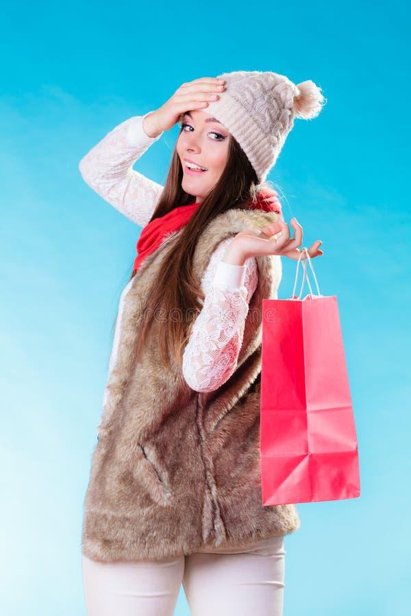 Женщина зимы с красной бумажной хозяйственной сумкой стоковые изображения rf