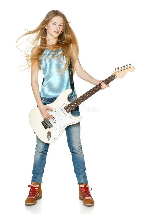 Женщина играя гитару внутри во всю длину стоковые изображения
