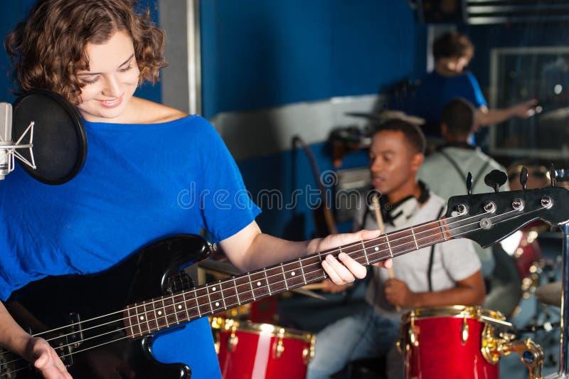Женщина играя гитару в студии звукозаписи стоковое изображение rf