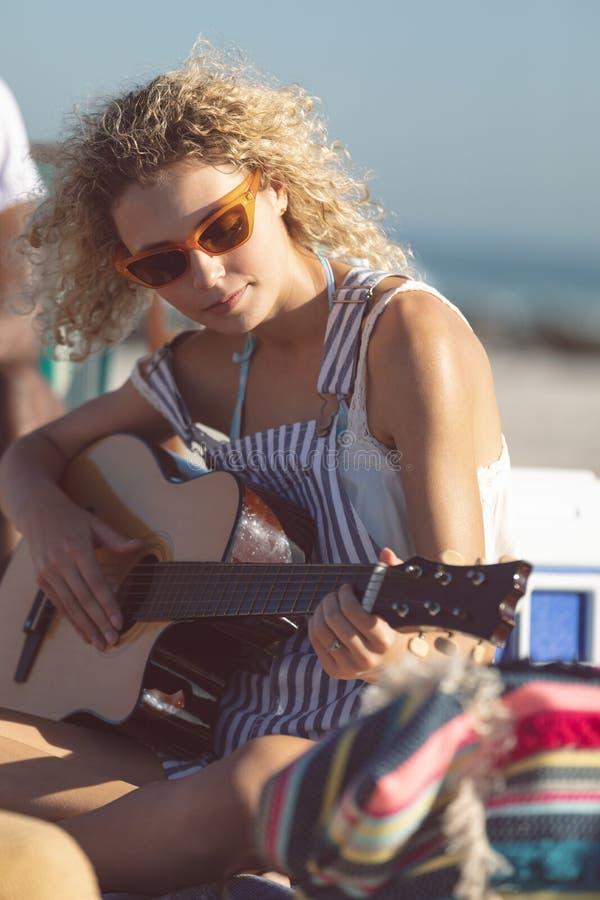 Женщина играя гитару на пляже стоковое фото