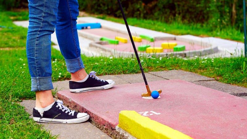 Женщина играя миниатюрный гольф на курсе стоковые изображения