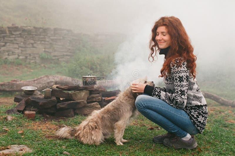 Женщина играя с бездомной собакой в лагере горы стоковые фотографии rf