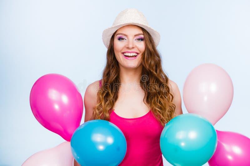Женщина играя с много красочных воздушных шаров стоковое фото