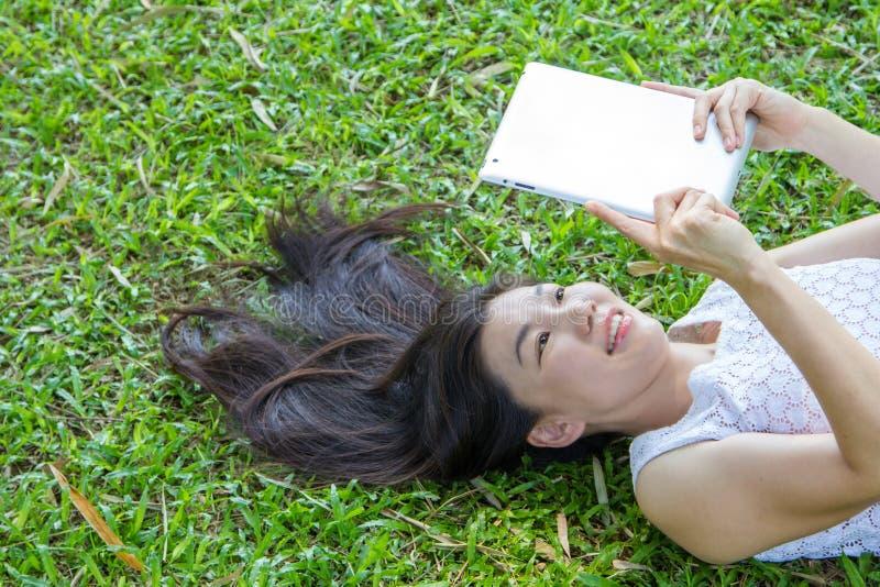 Женщина играя таблетку стоковая фотография rf