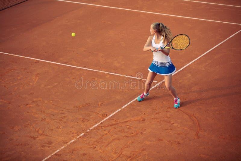 Женщина играя теннис на суде глины, с sporty обмундированием и здоровым образом жизни стоковое фото rf