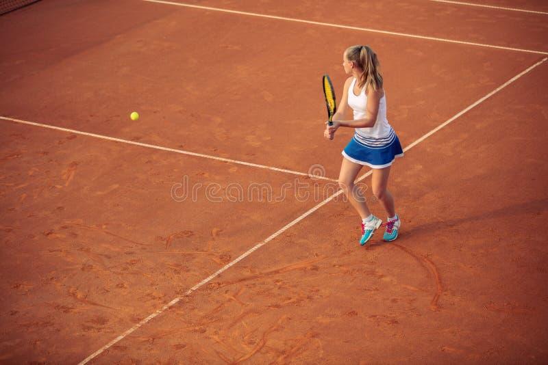 Женщина играя теннис на суде глины, с sporty обмундированием и здоровым образом жизни стоковое фото