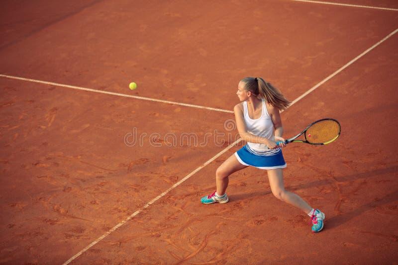 Женщина играя теннис на суде глины, с sporty обмундированием и здоровым образом жизни стоковое изображение