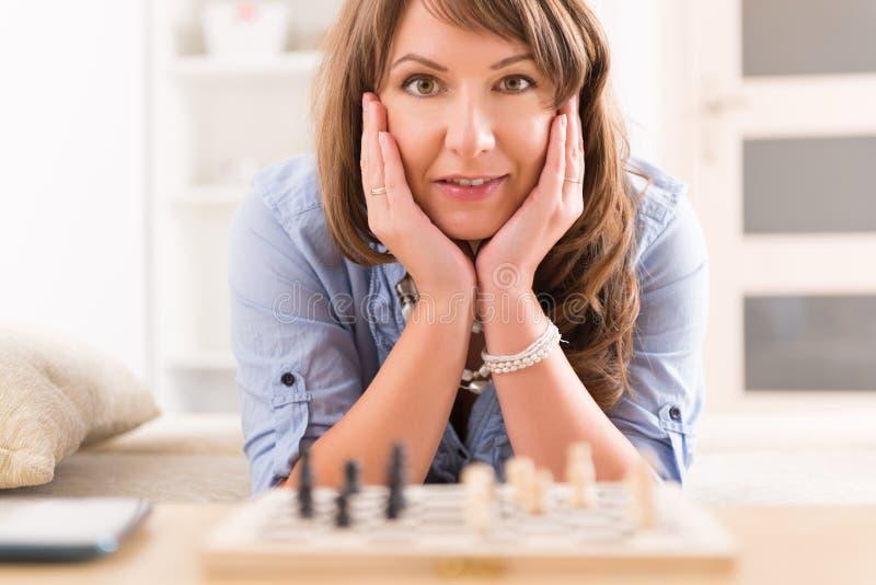 Женщина играя шахмат дома стоковые фото