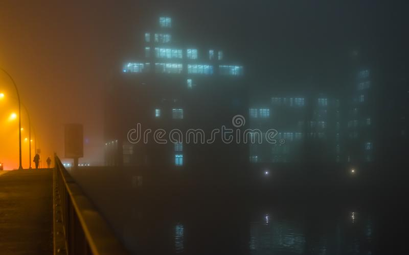 Женщина идет на туманную ночу над мостом стоковая фотография rf