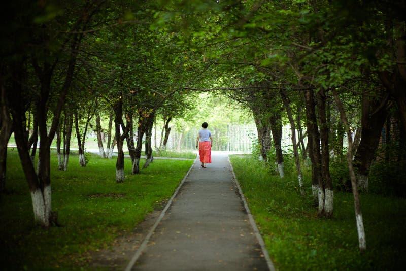 Женщина идет через переулок стоковые фотографии rf