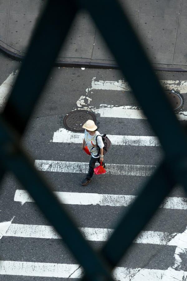 Женщина идя вдоль crosswalk пока носящ хозяйственные сумки, в районе Чайна-тауна Нью-Йорка в центре города стоковая фотография