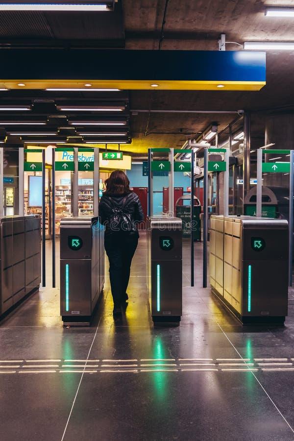 Женщина идя вне от платформы метро думала ворота дефлектора на станции стоковые фотографии rf