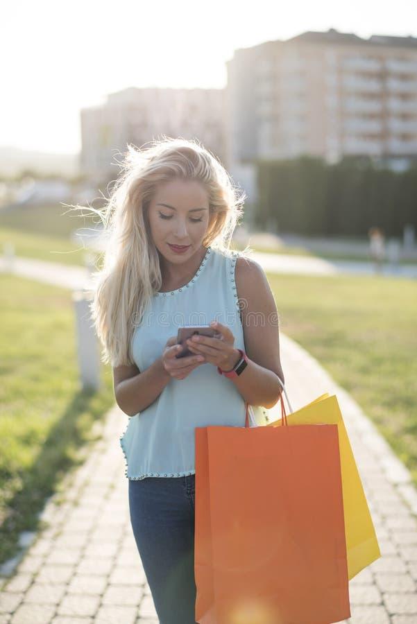 Женщина идя в парк с хозяйственными сумками и смотря smartphone стоковая фотография