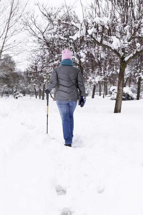 Женщина идя и имея потеху на холодный зимний день стоковая фотография