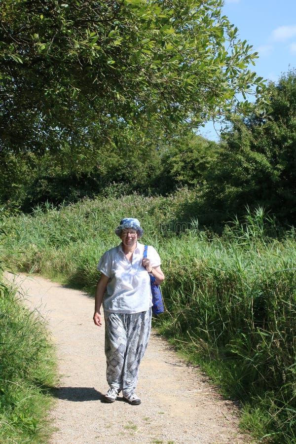 Женщина идя на тропу на заповеднике стоковая фотография