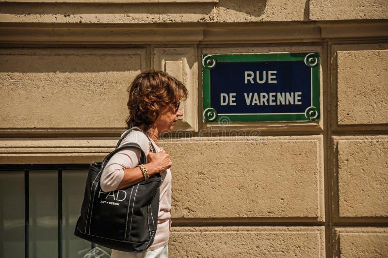 Женщина идя перед доской улицы в Париже стоковая фотография rf