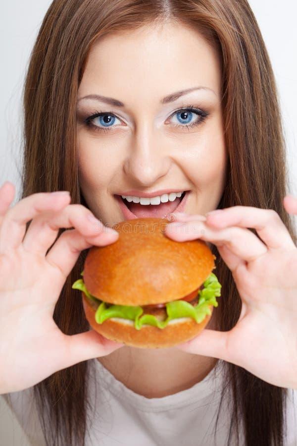 Женщина идя съесть гамбургер стоковое фото rf