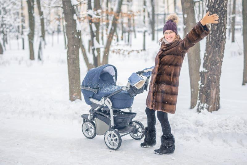 Женщина идя с прогулочной коляской в лесе на зиме стоковые изображения